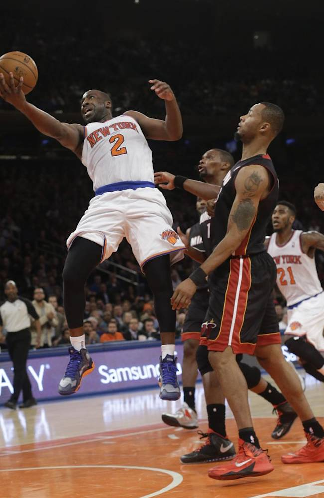 New York Knicks' Raymond Felton (2) drives past Miami Heat's Rashard Lewis during the first half of an NBA basketball game on Thursday, Jan. 9, 2014, in New York