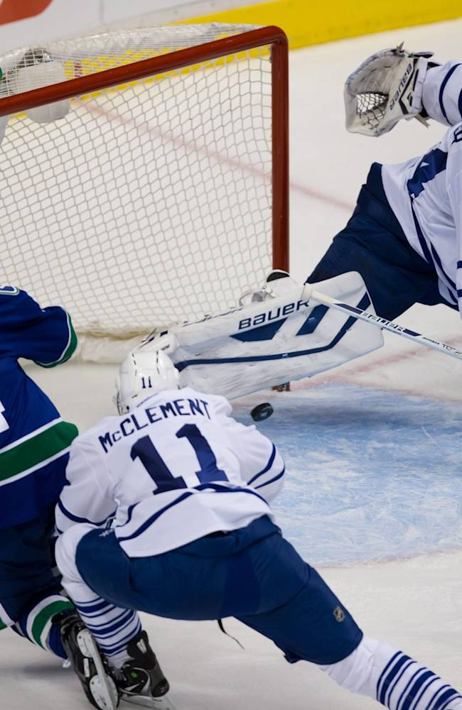 Toronto Maple Leafs goalie James Reimer, right, stops Vancouver Canucks' Alex Burrows, left, as Jay McClement defends during the first period of an NHL hockey game in Vancouver, British Columbia, on Saturday, Nov. 2, 2013