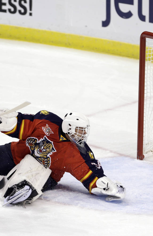 Florida Panthers goalie Tim Thomas (34) is unable to stop a shot by Boston Bruins' Dougie Hamilton as Boston Bruins defenseman Zdeno Chara (33) watches in the first period of an NHL hockey  game, Thursday, Oct. 17, 2013, in Sunrise, Fla