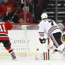 New Jersey Devils right wing Stephen Gionta (11) watches as a shot by teammate Jordin Tootoo, not pictured, enters the net of Chicago Blackhawks goalie Scott Darling, back right, during the first period of an NHL hockey game, Tuesday, Dec. 9, 2014, in New