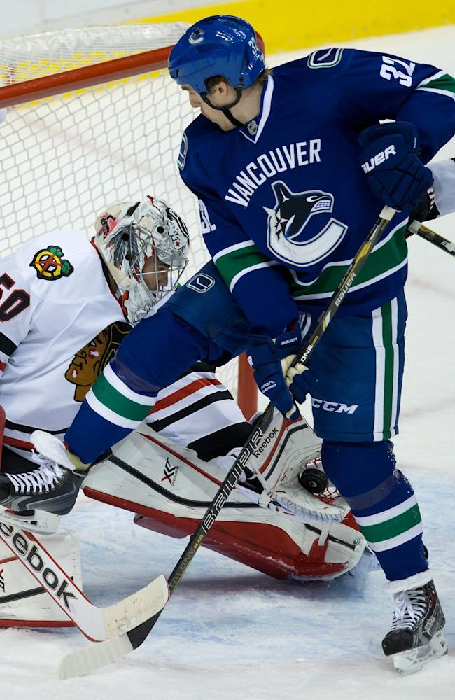 Chicago Blackhawks' goalie Corey Crawford, left, makes the save as Vancouver Canucks' Dale Weise, center, tries to tip the puck into the net while being checked by Blackhawks' Duncan Keith during third period NHL hockey action in Vancouver, British Columbia Saturday Nov. 23, 2013