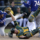 Oakland Athletics catcher Chris Gimenez, front, holds on to the ball after tagging out Texas Rangers' Alex Castellanos, left, who was caught stealing home, as Jose Felix, above right, looks on during the eighth inning of a spring training baseball game Sa