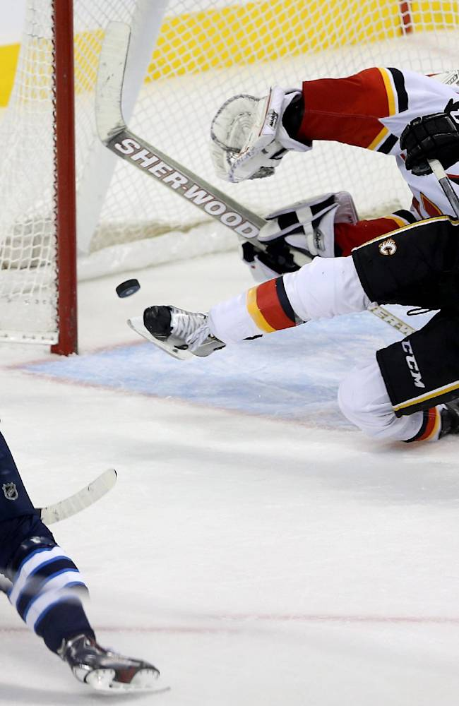 Winnipeg Jets' Bryan Little (18) scores a goal to tie the game with 5.6 seconds left against Calgary Flames' goaltender Reto Berra (29) and TJ Brodie (7) during third period NHL hockey action in Winnipeg Monday, Nov. 18, 2013