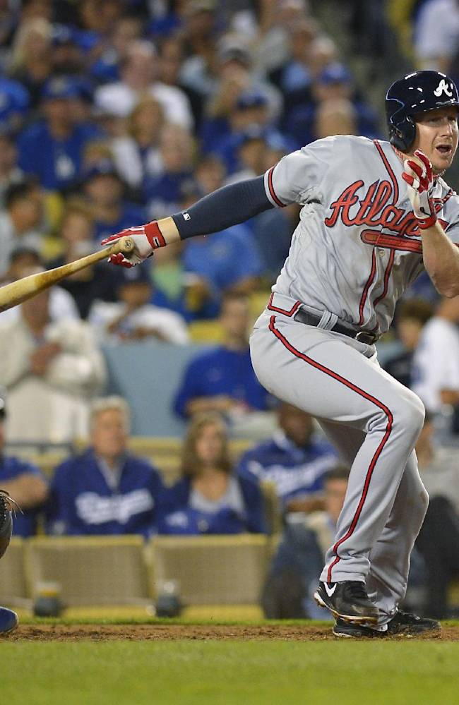 Atlanta Braves' Elliot Johnson follows through on a triple in the seventh inning of Game 4 in the National League baseball division series against the Los Angeles Dodgers, Monday, Oct. 7, 2013, in Los Angeles