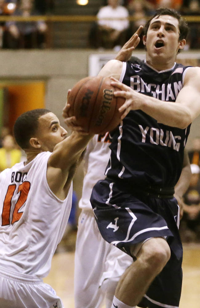 BYU's Matt Carlino, right, lays up a shot against Pacific's Andrew Bock in the second half of an NCAA college basketball game Thursday, Feb. 13, 2014, in Stockton, Calif