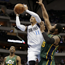 Dallas Mavericks' Monta Ellis (11) goes up for a shot against Utah Jazz's Derrick Favors (15) as Jeremy Evans (40) watch in the first half of an NBA basketball game, Friday, Feb. 7, 2014, in Dallas The Associated Press