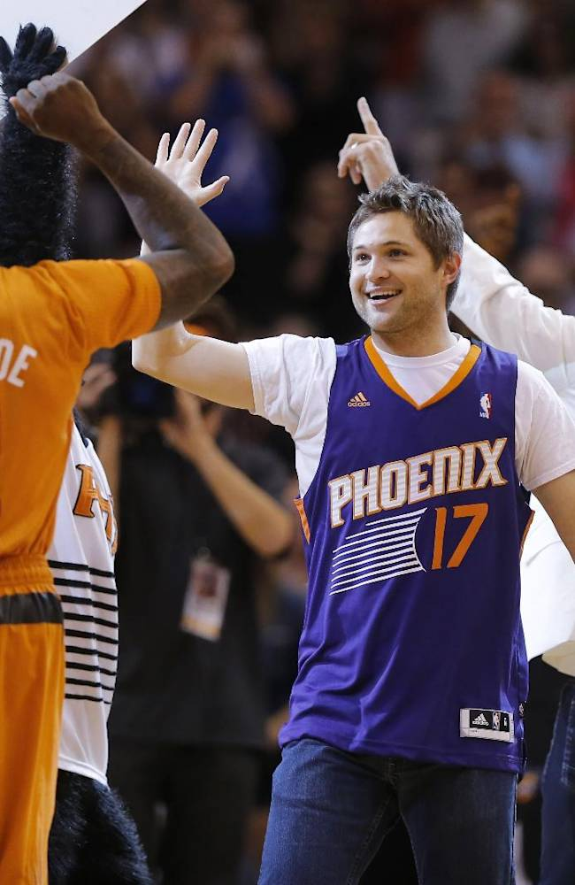 Phoenix Suns' Eric Bledsoe (2) high fives fan Tim Boven after Boven hit a three point field goal for $77,777 during a time out during the first half of an NBA basketball game against the New York Knicks, Friday, March 28, 2014, in Phoenix