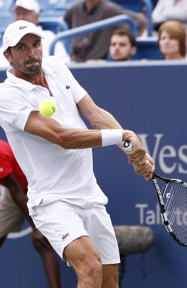 Julien Benneteau, from France, returns a volley to David Ferrer, from Spain, during a semifinal match at the Western & Southern Open tennis tournament, Saturday, Aug. 16, 2014, in Mason, Ohio
