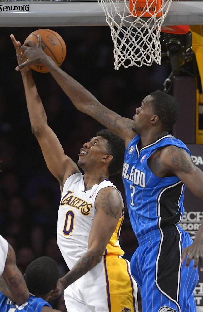Los Angeles Lakers forward Nick Young, left, has his shot blocked by Orlando Magic center Dewayne Dedmon during the second half of an NBA basketball game, Sunday, March 23, 2014, in Los Angeles. The Lakers won 103-94