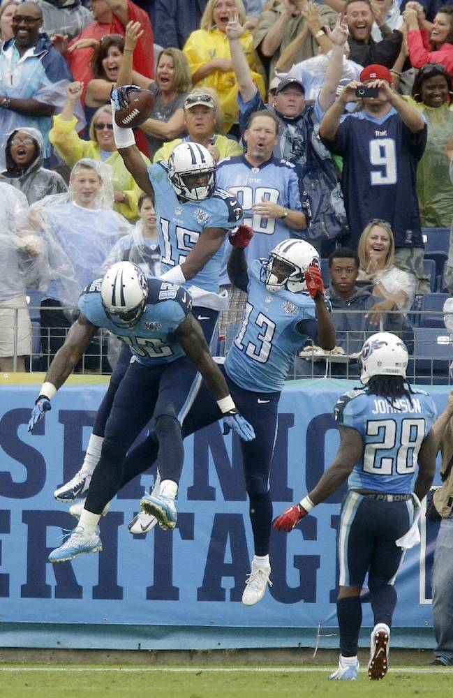 Tennessee Titans wide receiver Justin Hunter (15) celebrates with Delanie Walker (82) and Kendall Wright (13) after Hunter caught a 16-yard touchdown pass against the New York Jets in the second quarter of an NFL football game on Sunday, Sept. 29, 2013, in Nashville, Tenn. Titans running back Chris Johnson (28) runs to join in