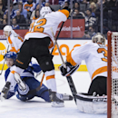 Toronto Maple Leafs' Nikolai Kulemin, left, gets dumped on the ice by Philadelphia Flyers' Mark Streit, center, during the second period of an NHL hockey game, Saturday, March 8, 2014 in Toronto The Associated Press