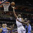 Charlotte Bobcats' Al Jefferson, center, shoots between Orlando Magic's Tobias Harris, left, and Dewayne Dedmon, right, during the first half of an NBA basketball game in Charlotte, N.C., Friday, April 4, 2014 The Associated Press