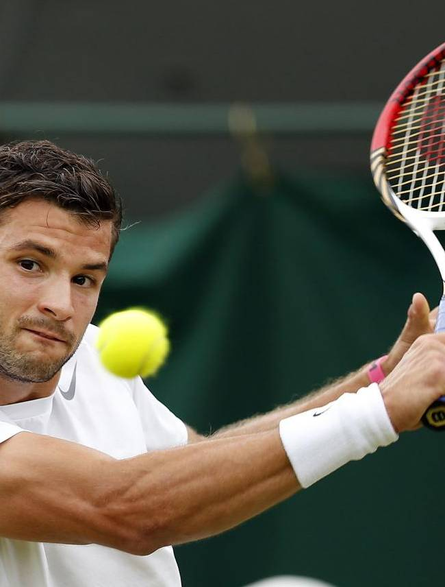 In this June 28, 2013, file photo, Grigor Dimitrov, of Bulgaria, plays a return to Grega Zemlja, of Slovenia, during a men's second-round singles match at the All England Lawn Tennis Championships in Wimbledon, London