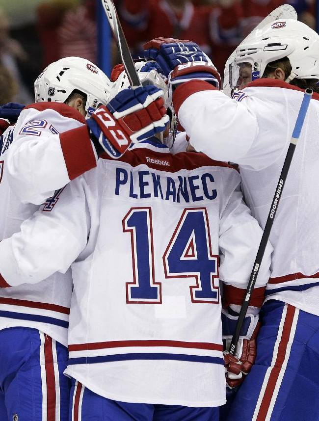 Montreal Canadiens players, including center Tomas Plekanec (14), of the Czech Republic, and defenseman Douglas Murray (6), celebrate a goal against the Tampa Bay Lightning by right winger Brendan Gallagher during the first period of an NHL hockey game Tuesday, April 1, 2014, in Tampa, Fla