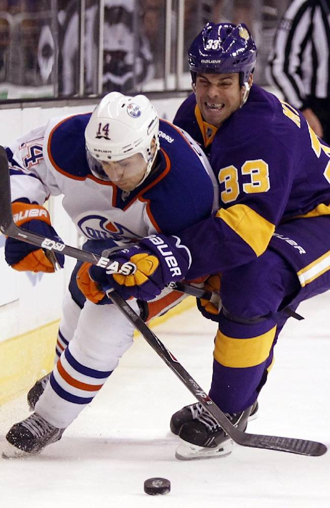 Edmonton Oilers right wing Jordan Eberle (14) battles Los Angeles Kings defenseman Willie Mitchell (33) for the puck during the third period of an NHL hockey game Sunday, Oct. 27, 2013, in Los Angeles. Kings won 2-1 in a shootout