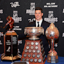 In this photo provided by the Las Vegas News Bureau, Sidney Crosby of the Pittsburgh Penguins poses with the Ted Lindsay Award for being voted most outstanding player in the league by the players, the Art Ross Trophy for leading the league in scoring poin