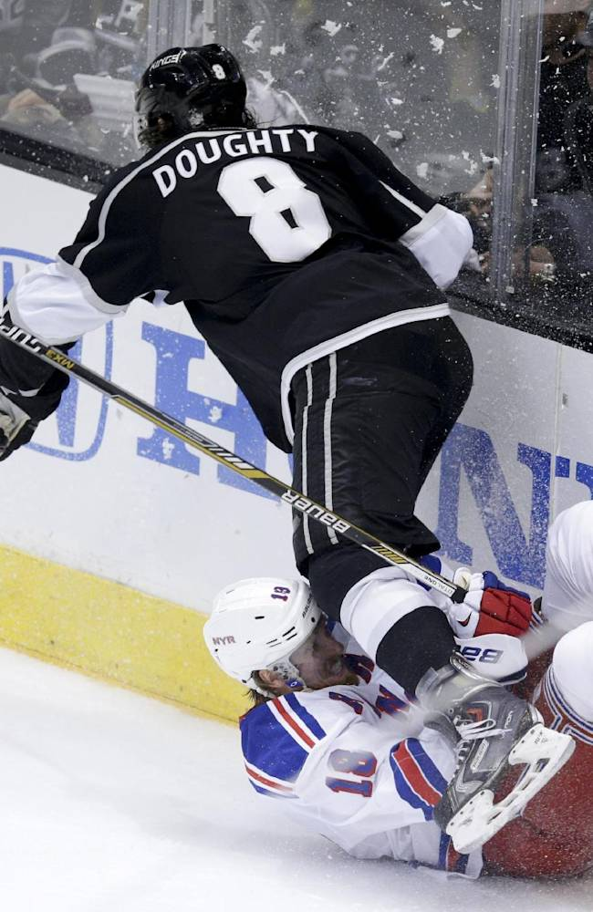 Los Angeles Kings defenseman Drew Doughty, top, goes over New York Rangers defenseman Marc Staal on his way to the puck during the second period of Game 2 in the NHL hockey Stanley Cup Finals in Los Angeles, Saturday, June 7, 2014
