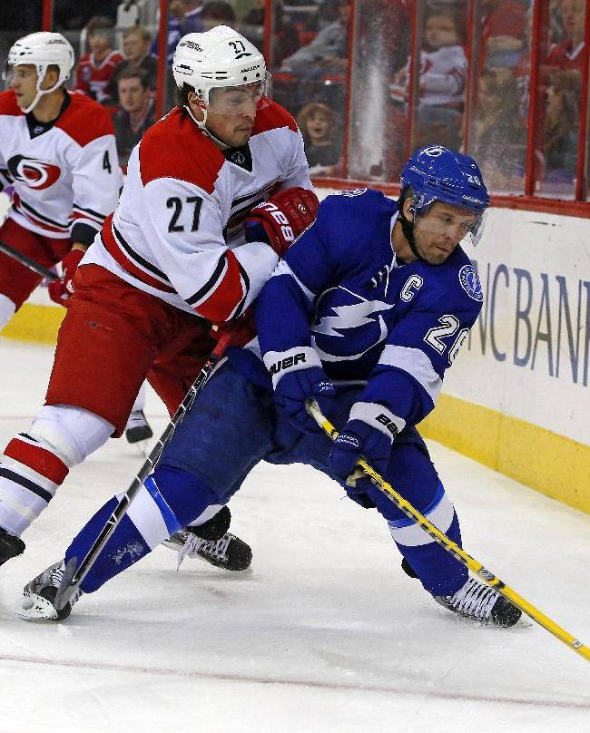 Tampa Bay Lightning's Martin St. Louis (26) tries to move the puck as Carolina Hurricanes' Justin Faulk (27) defends during the first period of an NHL hockey game, Friday, Nov. 1, 2013, in Raleigh, N.C