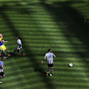 Swansea City's Jonjo Shelvey, left, has a shot towards goal past the Newcastle United players during their English Premier League soccer match at St James' Park, Newcastle, England, Saturday, April 19, 2014