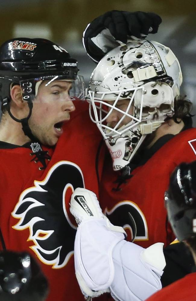 Calgary Flames' Chris Butler, left, and goalie Karri Ramo, from Finland, celebrate their team's win in NHL hockey action against the Phoenix Coyotes in Calgary, Canada, Wednesday, Jan. 22, 2014