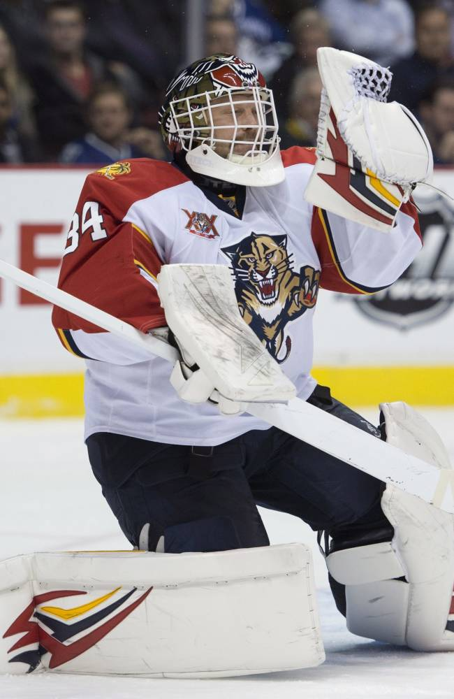 Florida Panthers goalie Tim Thomas (34) makes a save during first period NHL action against the Vancouver Canucks in Vancouver,  British Columbia, Tuesday, Nov. 19, 2013