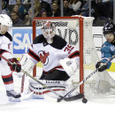 San Jose Sharks' Tyler Kennedy, right, is defended by New Jersey Devils' Jacob Josefson (16) and goalie Cory Schneider during the third period of an NHL hockey game Monday, Jan. 19, 2015, in San Jose, Calif. New Jersey won 5-2 The Associated Press