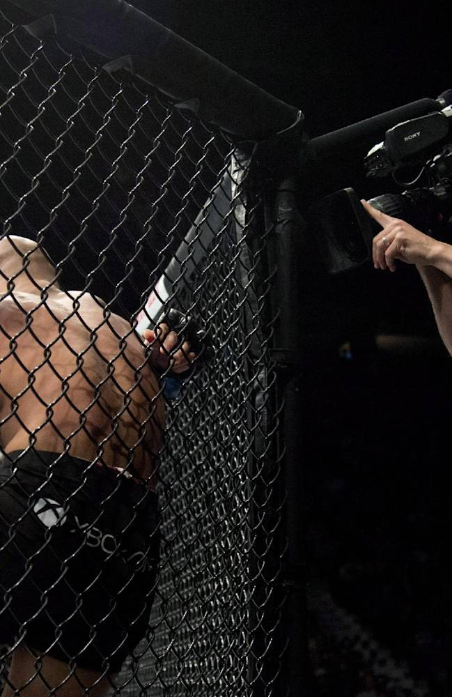 A television cameraman shoots Demetrious Johnson, of the United States, centre, and Ali Bagautinov, of Russia, during the flyweight bout at UFC 174 in Vancouver, British Columbia, Saturday, June, 14, 2014