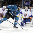 San Jose Sharks' Martin Havlat (9), of Czech Republic, controls the puck in front of New York Islanders goalie Kevin Poulin, right, and Thomas Hickey (14) during the first period of an NHL hockey game on Tuesday, Dec. 10, 2013, in San Jose, Calif. (AP Photo/Marcio Jose Sanchez)