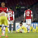Players leave the field at the end of a Champions League, group F soccer match, at the Naples San Paolo stadium, Italy, Wednesday, Dec. 11, 2013. Ten-man Arsenal advanced to the Champions League knockout phase for the 14th consecutive year despite a 2-0 l