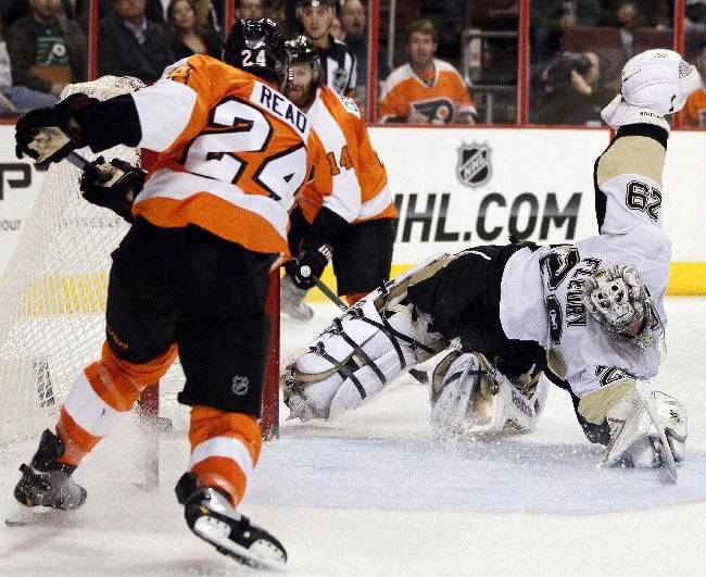 Philadelphia Flyers' Mattt Read, left, scores against a diving Pittsburgh Penguins goalie Marc-Andre Fleury during the second period of an NHL hockey game, Saturday, March 15, 2014, in Philadelphia