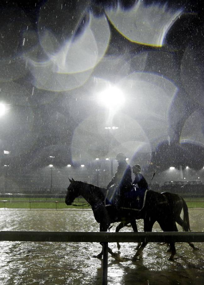 Exercise rider Abel Flores takes Kentucky Derby hopeful Tapiture for a morning workout in the rain at Churchill Downs Monday, April 28, 2014, in Louisville, Ky