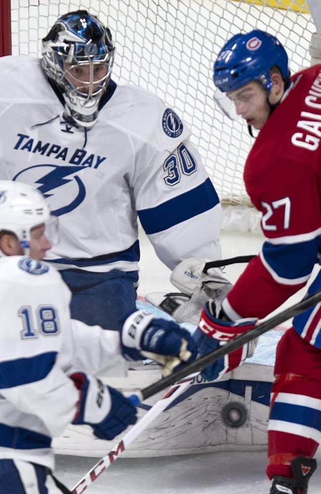 Montreal Canadiens' Alex Galchenyuk looks for the rebound on a save by Tampa Bay Lightning goalie Ben Bishop as Lightning's Ondrej Palat watches during the second period of an NHL hockey game Tuesday, Nov. 12, 2013, in Montreal