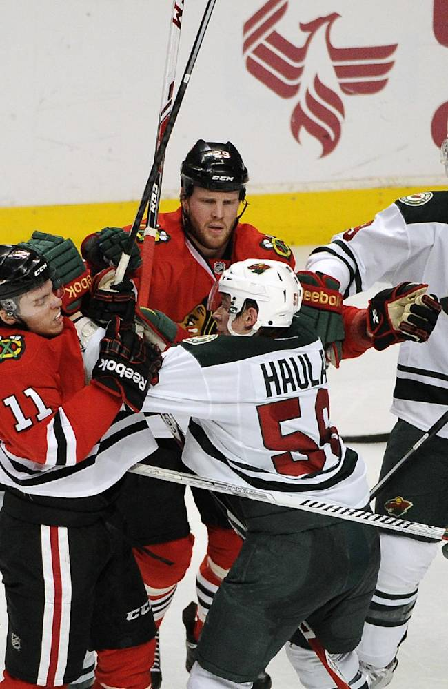 Chicago Blackhawks' Jeremy Morin (11) and Minnesota Wild's Erik Haula (56) get into an altercation in the second period of an NHL hockey game in Chicago, Thursday, April 3, 2014