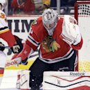 Chicago Blackhawks goalie Corey Crawfod, right, blocks a shot by Calgary Flames center Paul Byron (32) during the first period of an NHL hockey game in Chicago, Wednesday, Oct. 15, 2014 The Associated Press