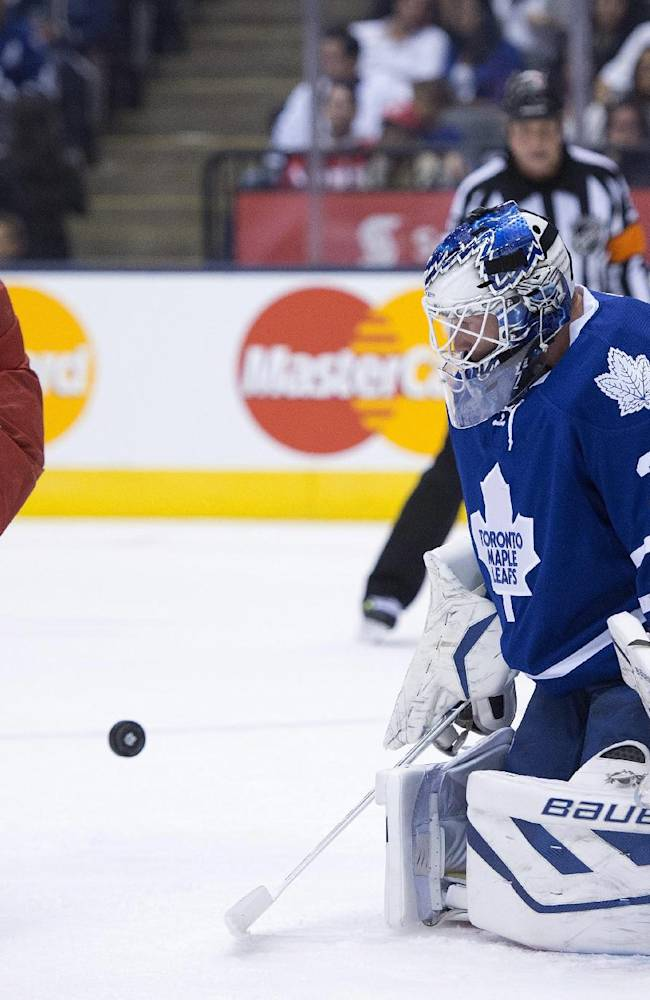 Toronto Maple Leafs goaltender James Reimer makes a save as Detroit Red Wings' Riley Sheahan looks for the rebound during first-period preseason NHL hockey game action in Toronto, Saturday Sept. 28, 2013