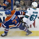 San Jose Sharks' Justin Braun (61) is checked by Edmonton Oilers' Boyd Gordon (27) during the first period of an NHL hockey game, Friday, Nov. 15, 2013 in Edmonton, Alberta The Associated Press