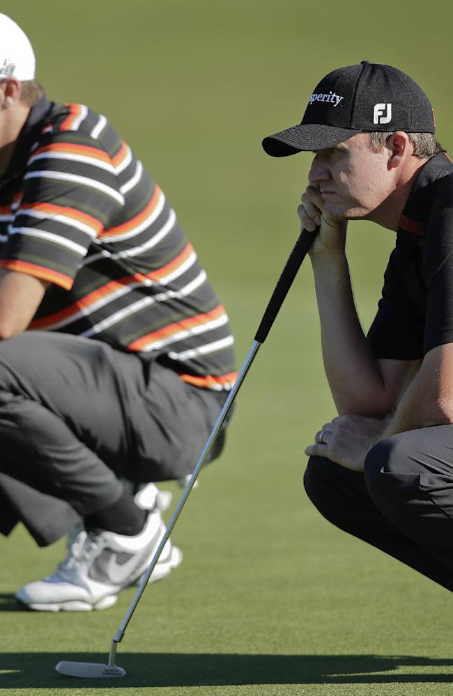 Jimmy Walker, right, and Nick Watney line up their putts on the 14th green in the first round of the Shriners Hospitals for Children Open golf tournament, Thursday, Oct. 17, 2013, in Las Vegas