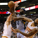 Memphis Grizzlies' Zach Randolph (5) shoots between Phoenix Suns' Miles Plumlee, left, and P.J. Tucker during the first half of an NBA basketball game, Monday, April 14, 2014, in Phoenix The Associated Press