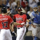 Atlanta Braves left fielder Justin Upton (8) celebrates with teammates Jordan Schafer (17) and Andrelton Simmons (19) after hitting a grand slam in the seventh inning of a baseball game against the Los Angeles Dodgers Friday, May 17, 2013 in Atlanta.  Dodgers catcher A.J. Ellis looks on at right. (AP Photo/John Bazemore)