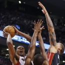 Toronto Raptors' Rudy Gay, left, shoots against Miami Heat's Chris Bosh, center, and Michael Beasley, right, during the second half of an NBA basketball game in Toronto, Friday, Nov. 29, 2013 The Associated Press