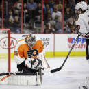 Philadelphia Flyers' Steve Mason, left, blocks a shot by Chicago Blackhawks' Brandon Saad during the first period of an NHL hockey game, Wednesday, March 25, 2015, in Philadelphia. Philadelphia won 4-1. (AP Photo/Matt Slocum)