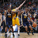 Utah Jazz gurd Alec Burks, right, works past Denver Nuggets forward Jan Vesely, center, of the Czech Republic, with help from pick set by Jazz center Derrick Favors in the third quarter of the Nuggets' 101-94 victory in an NBA basketball game in Denver on