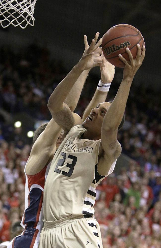 Oakland's Tommy McCune (23) attempts a layup against Gonzaga's Drew Barham during the second half of an NCAA basketball game, in Spokane, Wash., on Sunday, Nov. 17, 2013. Gonzaga won 82-67