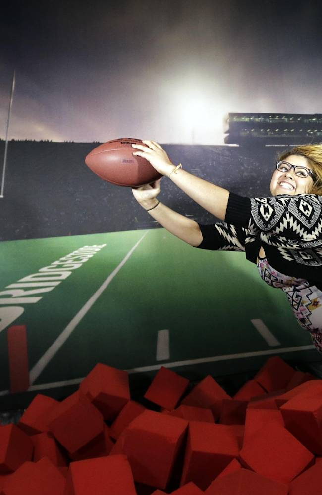 Denise Gonzalez, of New York, makes a diving catch over foam blocks for a photo during events on Super Bowl Boulevard, Friday, Jan. 31, 2014, in New York. The Seattle Seahawks are scheduled to play the Broncos in NFL football's Super Bowl on Sunday in East Rutherford, N.J