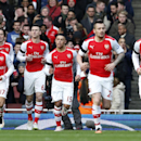 Arsenal's Laurent Koscielny, third left no. 6, runs back with teammates after scoring the opening goal during their English Premier League soccer match between Arsenal and Stoke City at the Emirates stadium in London, Sunday, Jan. 11, 2015