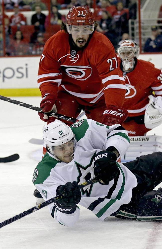 Dallas Stars' Tyler Seguin (91) falls to the ice while chasing the puck against Carolina Hurricanes' Justin Faulk (27) during the first period of an NHL hockey game in Raleigh, N.C., Thursday, April 3, 2014