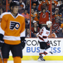 New Jersey Devils' Travis Zajac, right, celebrates after scoring a goal as Philadelphia Flyers' Vincent Lecavalier skates past during the first period of an NHL hockey game, Tuesday, March 11, 2014, in Philadelphia The Associated Press