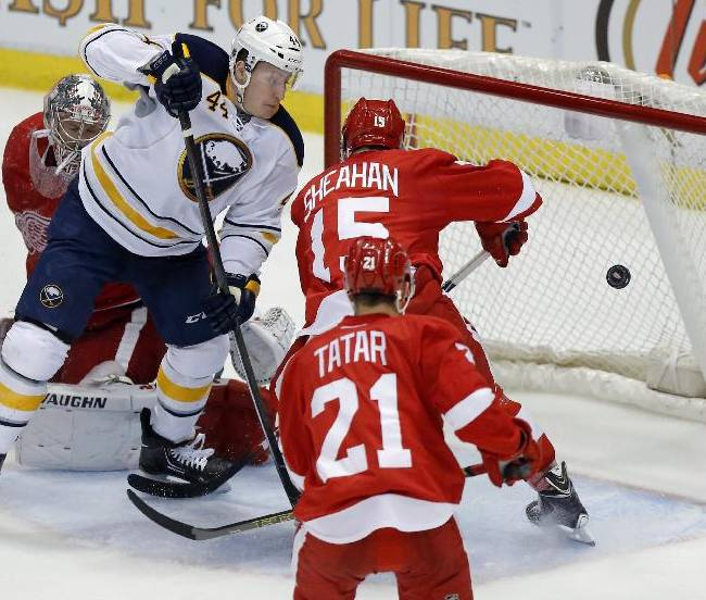 Buffalo Sabres' Nicolas Deslauriers (44) shot on goal is deflected by Detroit Red Wings' Riley Sheahan (15) during the third period of an NHL hockey game Friday, April 4, 2014, in Detroit. The Red Wings defeated the Sabres 3-2