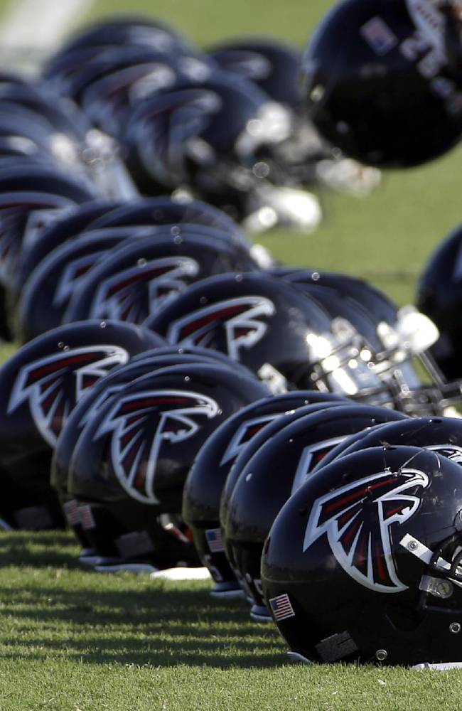 Atlanta Falcons football players helmets are lined up on the ground during an NFL training camp practice Wednesday, Aug. 13, 2014, in Houston. The Falcons are practicing with the Houston Texans this week before their preseason game Saturday