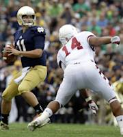 Notre Dame quarterback Tommy Rees (11) drops back to throw a touchdown pass to DaVaris Daniels over Temple linebacker Jarred Alwan (14) during the first half of an NCAA college football game in South Bend, Ind., Saturday, Aug. 31, 2013. (AP Photo/Michael Conroy)